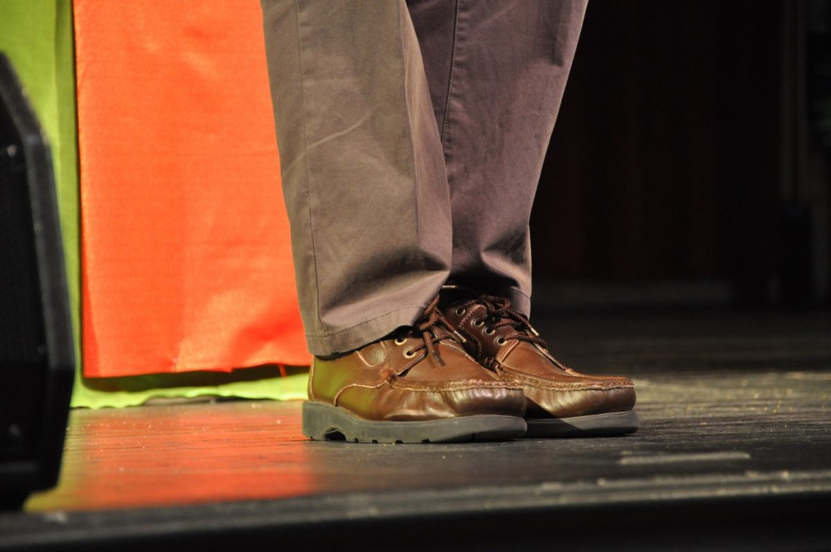 Man's legs on a stage. He is wearing loafers and casual brown dress pants.