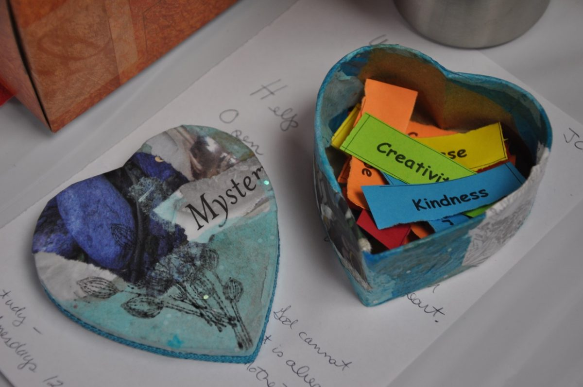 "Decorated heart-shaped cardboard box open containing words on colored pieces of paper with the lid laying beside it. The words you can see are ""creativity"" and ""kindness."" The lid has part of the word ""Mystery"" showing on it."