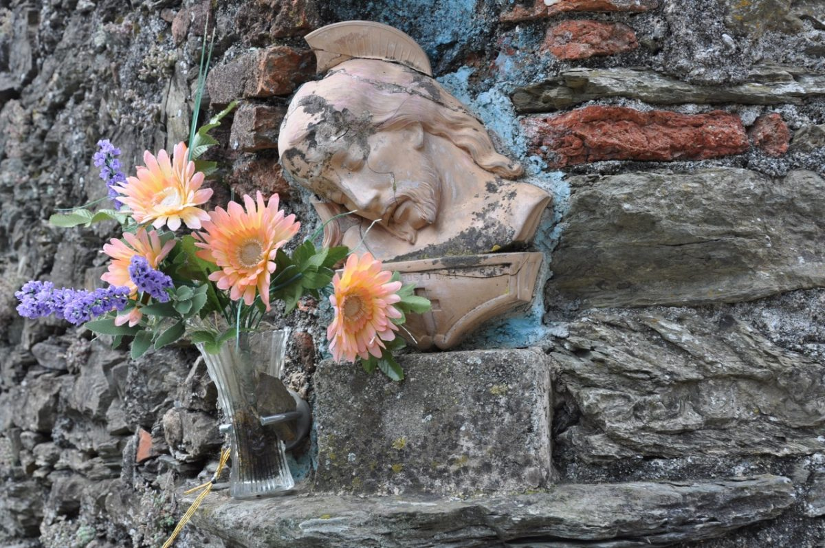 Bas relief sculpted head of Christ in a rock wall with a vase of flowers next to it.