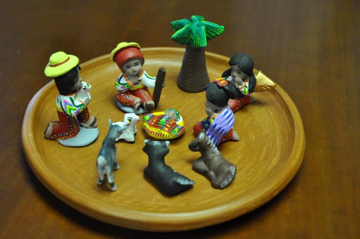 A miniature Latin American nativity set on a small wooden plate.