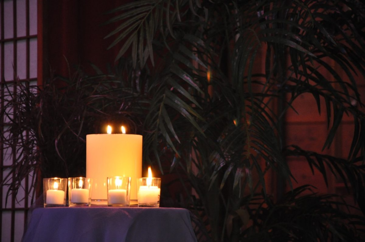 4 Advent votives lit surrounding the Christmas Eve lit pillar candle on a purple table cloth in front of some indoor trees.