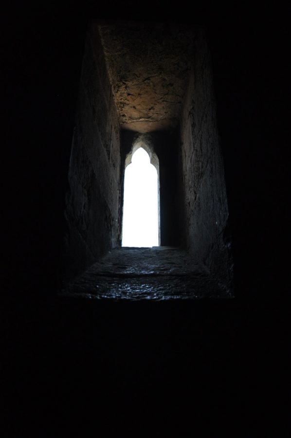 The outline of a window to a white sky, looking from below the window through stone walls.