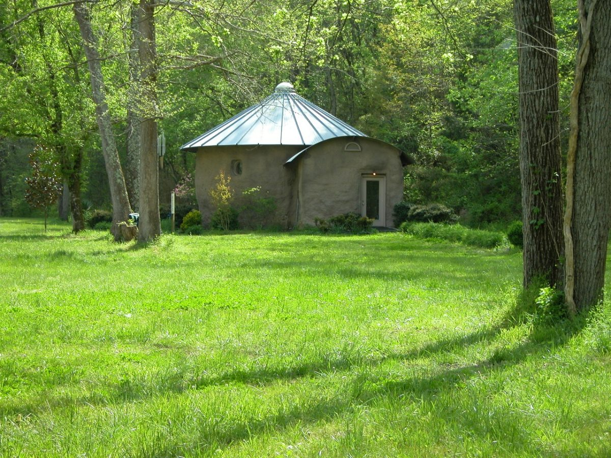 Small, round stone chapel at the edge of a green, grassy meadow with several trees around it.