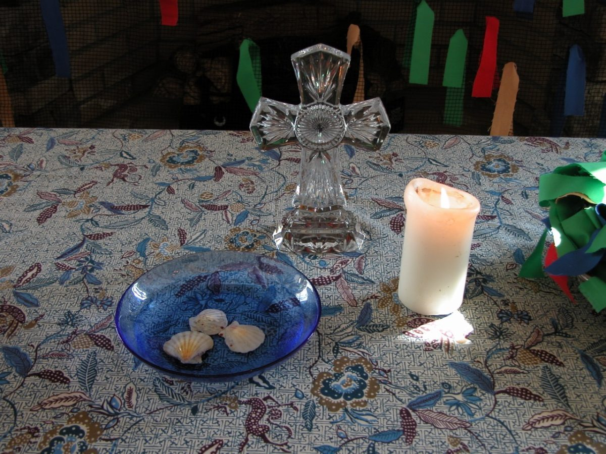 A glass cross, behind a small blue bowl with three sea shells, and a lit pillar candle all sitting on a table covered with a tablecloth.
