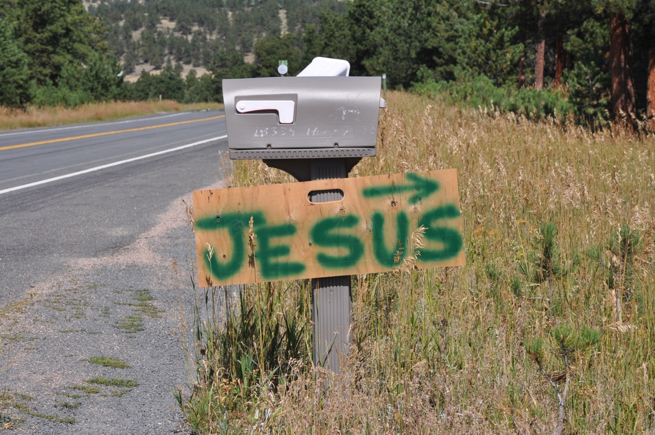 """A hand-painted sign with """"Jesus"""" and an arrow posted on a mailbox on the side of a rural highway."""