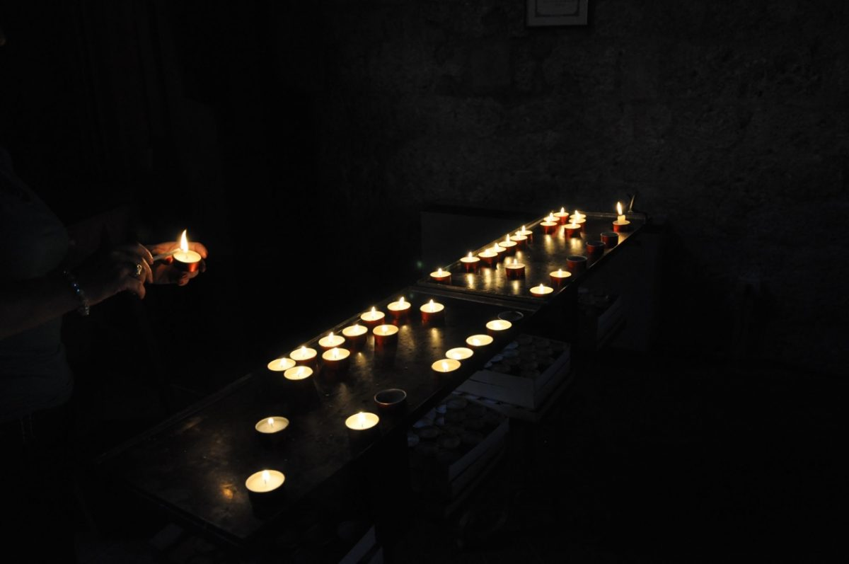 Two tables (altars?) with a number of lit candles in a dark room. Someone preparing to set another lit candle down.