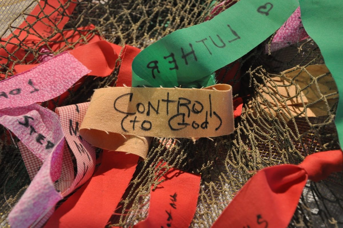 """Strips of colored material with words and phrases written on them. Phrase in the center says """"Control (to God)."""""""